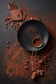 Kakaopulver in einem sieb auf einem schwarzen teller, dunkle oberfläche mit schokolade
