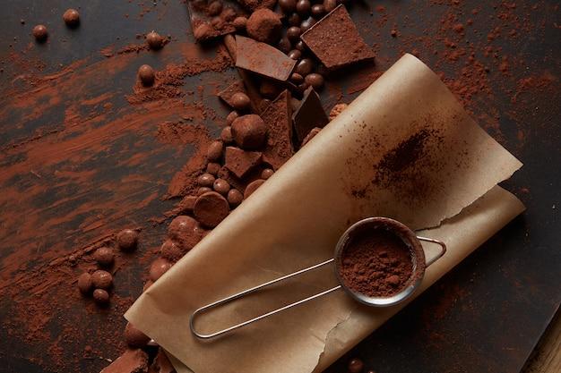 Kakaopulver in einem sieb auf pergament mit schokolade auf einem dunklen hintergrund