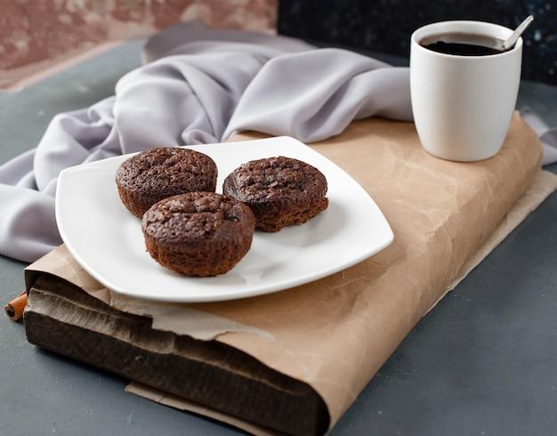 Kakaoschokoladenkuchen in einer weißen platte mit einer tasse tee