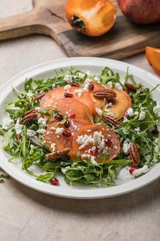Kaki-salat mit rucola, nüssen, ziegenkäse, granatapfel. gesundes vegetarisches lebensmittelkonzept.