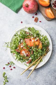 Kaki-salat mit rucola, nüssen, ziegenkäse, granatapfel. gesundes vegetarisches nahrungsmittelsalatkonzept.