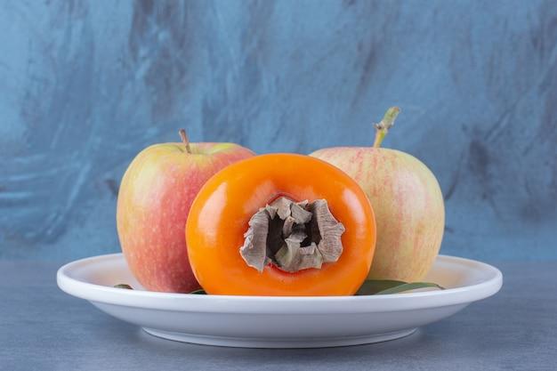 Kaki und äpfel auf teller auf der dunklen oberfläche