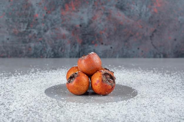 Kakis mit kokosnusspulver auf marmoroberfläche verteilt