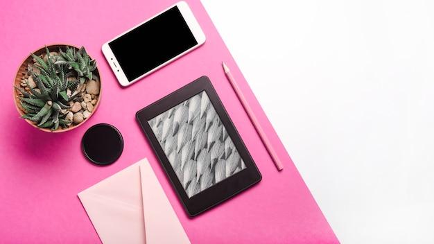Kaktus-topfpflanze; mobiltelefon; ebook reader; bleistift; umschlag auf rosa und weißem hintergrund