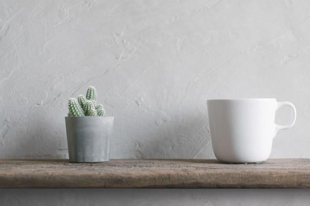 Kaktusblume mit weißer kaffeetasse auf modernem innenhintergrund der hölzernen wand-regale.