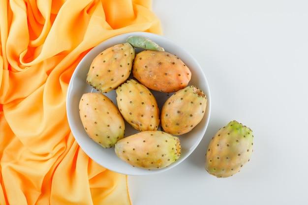 Kaktusfrüchte in einem weißen teller auf gelber textiloberfläche