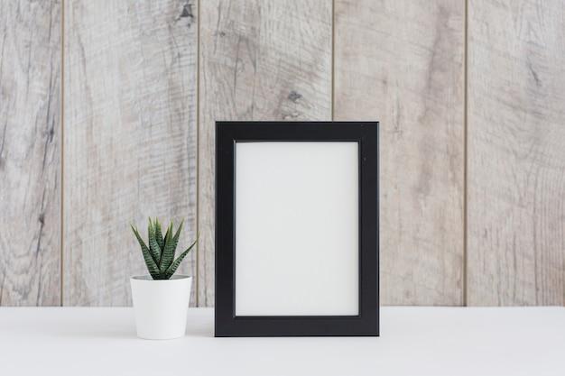 Kaktuspflanze im weißen topf mit dem leeren bilderrahmen gegen hölzerne wand