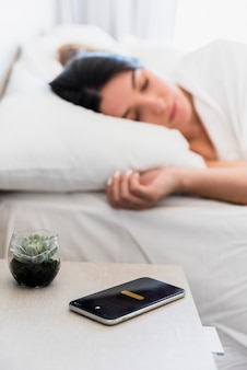 Kaktuspflanze und smartphone auf tabelle nahe der frau, die auf bett schläft