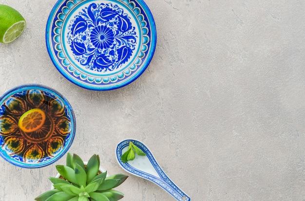 Kaktuspflanze; zitronen- und minzteetasse im orientalischen blumenmuster auf strukturiertem hintergrund