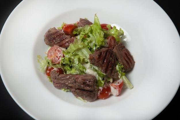Kalbsalat, salat mit großen kalbsscheiben und frischem gemüse auf einem teller auf schwarzem grund.
