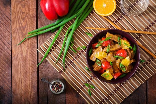 Kalbsfilet - mit orangen und paprika in süß-saurer sauce auf einem holztisch anbraten. flach liegen. draufsicht