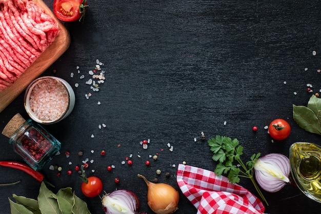 Kalbsfilet und hackfleisch auf einem holzbrett mit kirschtomaten, paprika und kräutern.