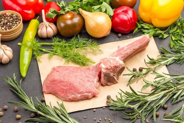 Kalbsfleisch auf knochen auf einem stück papier und einem satz gemüse und gewürze