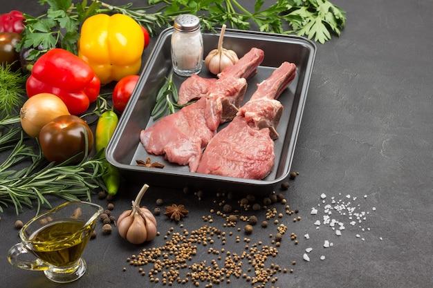 Kalbsfleisch auf knochen, knoblauch und salz in einer lebensmittelmetallpalette mit gemüse und gewürzen.
