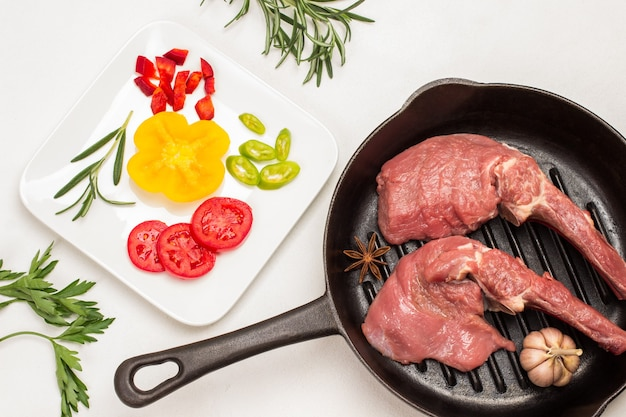 Kalbsfleisch auf knochen, knoblauch und sternanis in einer pfanne mit geschnittenen tomaten und paprika auf weißem teller