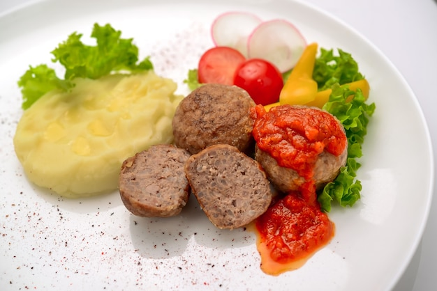 Kalbsfleischbällchen mit reis und tomatensauce auf dem hintergrund von kartoffelpüree