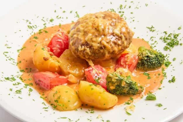 Kalbsschnitzel mit speck, kapern, geriebenem käse in einer cremigen sauce