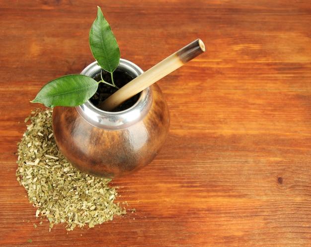 Kalebasse und bombilla mit yerba mate auf holztisch