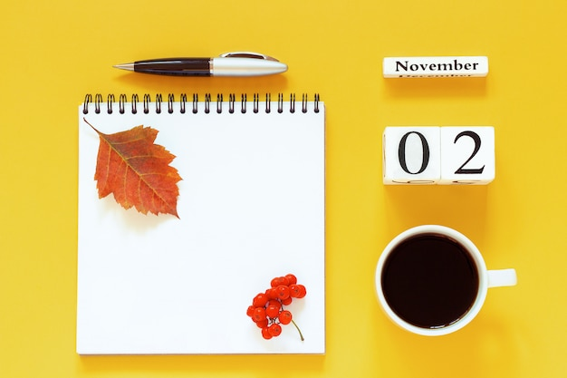 Kalender 2. november tasse kaffee, notizblock mit stift und gelbes blatt auf gelb
