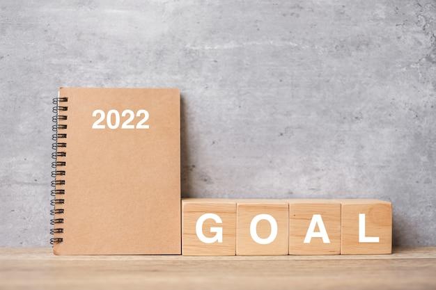 Kalender 2022 mit goal-block auf holztisch. frohes neues jahr, motivation, auflösung, aufgabenliste, start, strategie und plankonzept