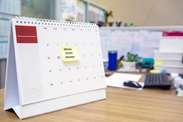 Kalender auf dem schreibtisch mit papiernotiz von zu hause aus.