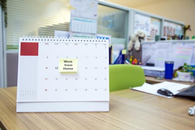 Kalender auf dem schreibtisch mit papiernotiz von zu hause aus