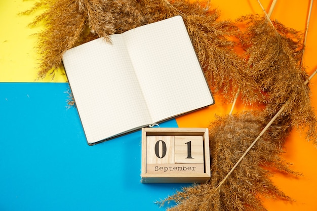 Kalender aus holzwürfeln mit zahlen und monaten. notizblock mit weißen blättern. der erste tag des schuljahres. eine zahl auf einem holzkalender wählen. september 1. september datum