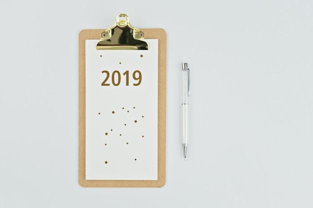 Kalender des neuen jahres 2019 mit notizbuch und stift auf weiß