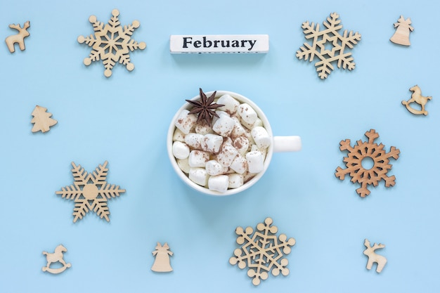 Kalender-februar-becher-kakaoeibische und große hölzerne schneeflocken