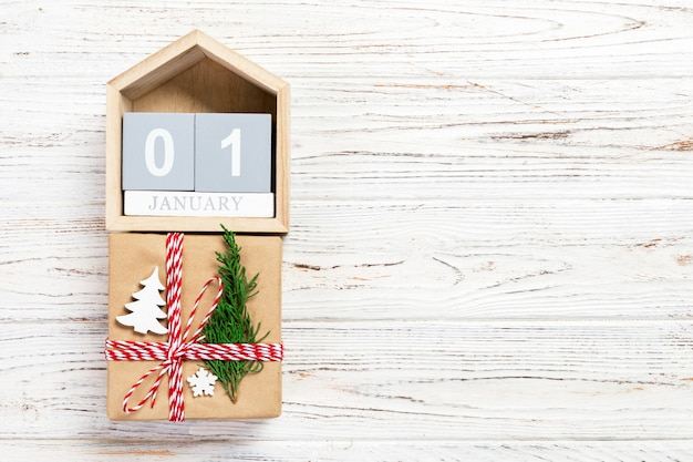 Kalender mit datum 1. januar und geschenkboxen auf farbigem hintergrund. weihnachtskonzept