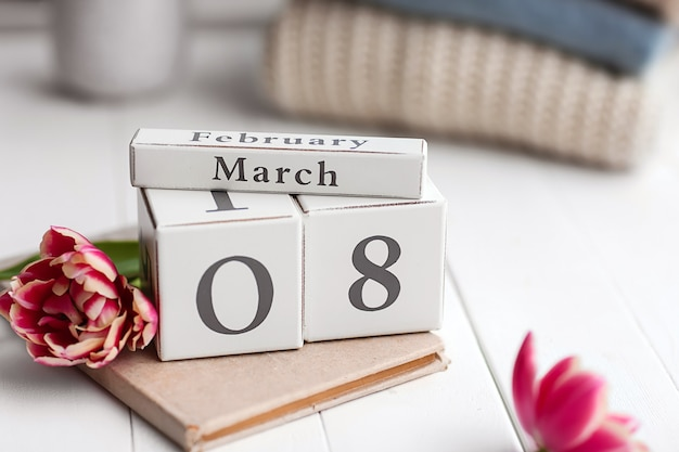 Kalender mit datum vom 8. märz, buch und blume auf weißem tisch