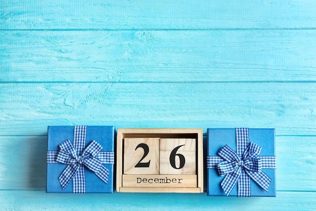 Kalender mit datums- und geschenkboxen auf farbiger oberfläche. weihnachtskonzept