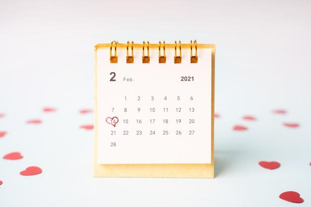 Kalender mit dem markierten tag des 14. februar auf einem blauen hintergrund unter den herzen