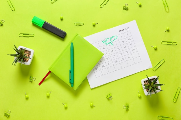 Kalender mit markiertem datum des aprilscherz und briefpapier auf der farboberfläche