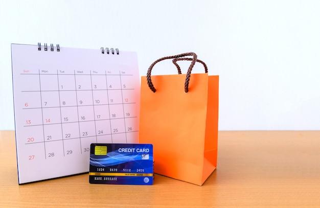 Kalender mit tagen und kreditkarte und orange papiertüte auf holztisch. einkaufskonzept