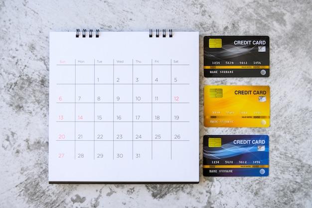 Kalender mit tagen und kreditkarten auf dem tisch. einkaufskonzept
