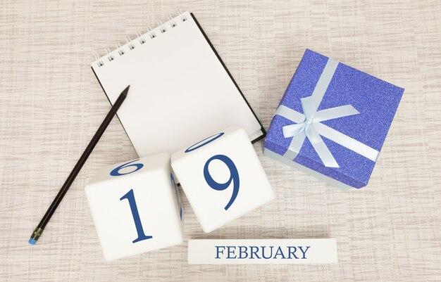 Kalender mit trendigen blauen text und zahlen für den 19. februar und ein geschenk in einer box.