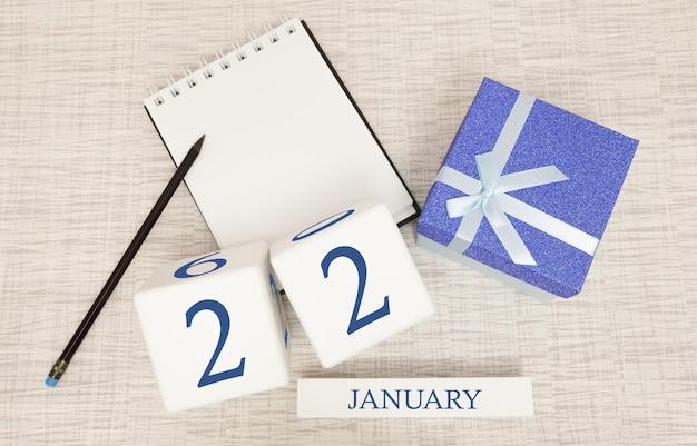Kalender mit trendigen blauen text und zahlen für den 22. januar und ein geschenk in einer box