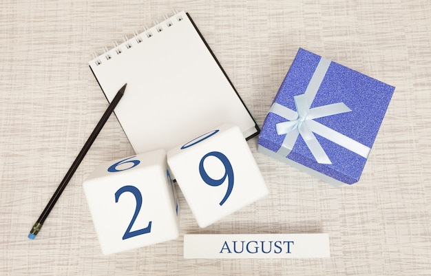 Kalender mit trendigen blauen text und zahlen für den 29. august und ein geschenk in einer box.