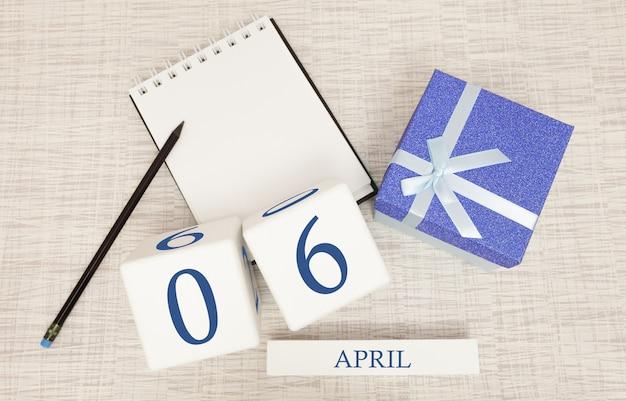 Kalender mit trendigen blauen text und zahlen für den 6. april und ein geschenk in einer box.