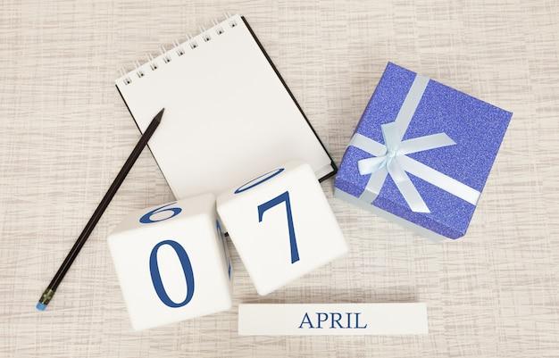 Kalender mit trendigen blauen text und zahlen für den 7. april und ein geschenk in einer box.