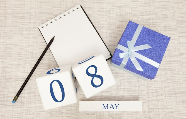 Kalender mit trendigen blauen text und zahlen für den 8. mai und ein geschenk in einer box.