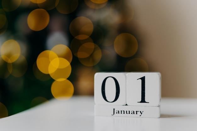 Kalender mit zahlen und monat auf weißem schreibtisch gegen glänzende lichter und neues jahr