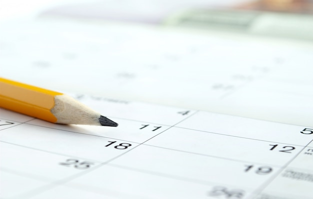 Kalender und bleistift zur markierung des gewünschten datums