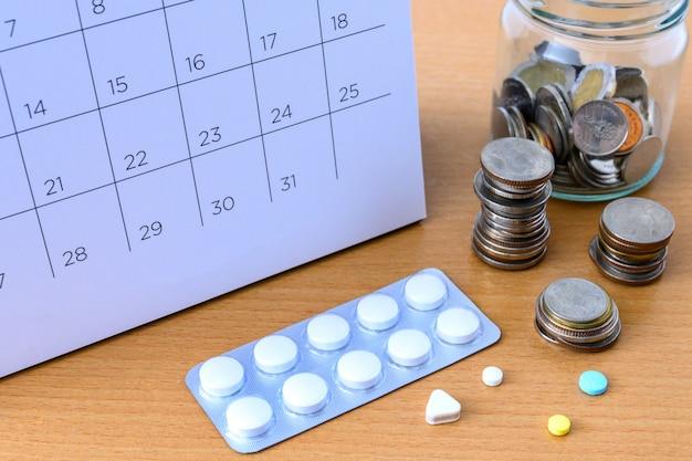 Kalender und drogen und münzen auf dem tisch. konzept gesundheitswesen