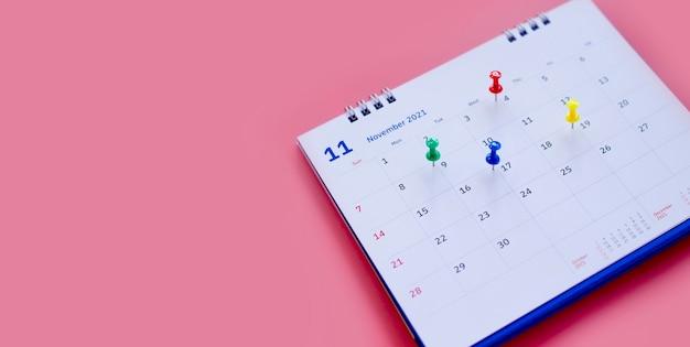 Kalender und terminplaner mit einem pin auf rosa hintergrund.
