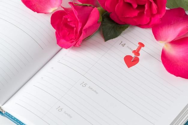Kalender-valentinsgrußtagesrosastift und rote rosen auf kalendernotizbuch. liebesterminkonzept