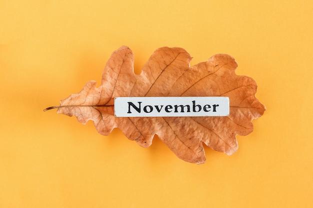 Kalendermonat november auf herbsteichenblatt auf gelbem hintergrund.