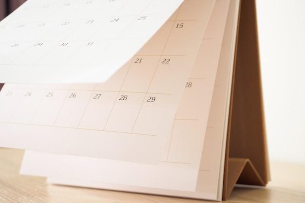 Kalenderseite, die blatt auf holztabellenhintergrund-geschäftsplanplanungs-termin-besprechungskonzept umdreht