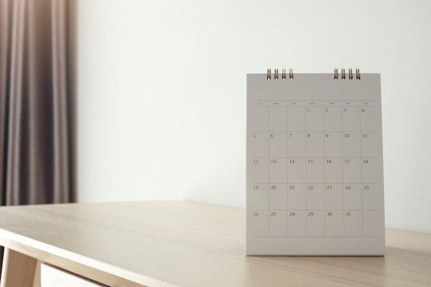 Kalenderseite schließen oben auf holztisch auf weißer wand